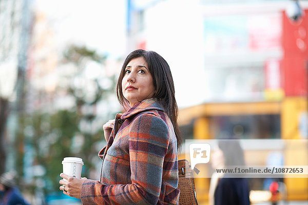Mature female tourist with takeaway coffee on city street  Tokyo  Japan