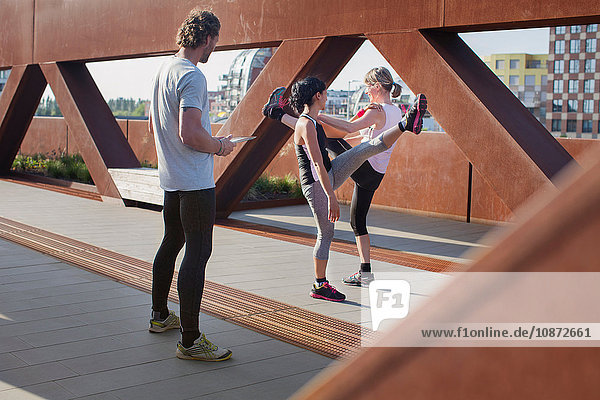 Two women training on urban footbridge with male personal trainer
