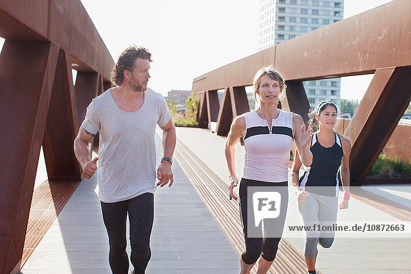 Female runners running on urban footbridge with personal trainer