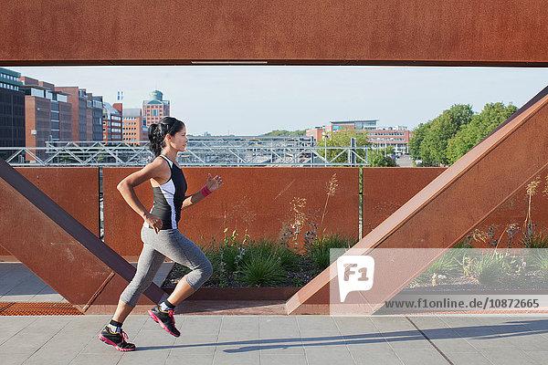 Weibliche Läuferin läuft auf städtischer Fußgängerbrücke