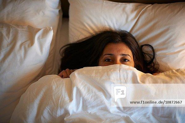Porträt einer reifen Frau  die nachts aus dem Hotelbett schaut