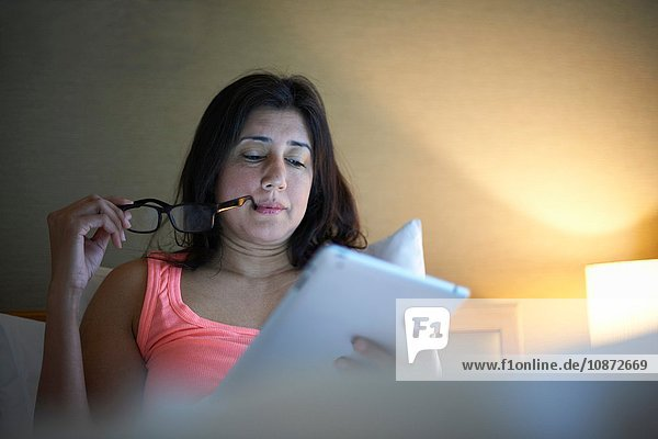 Mature businesswoman reading digital tablet in hotel bed at night