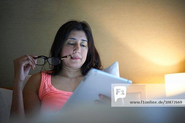 Reife Geschäftsfrau liest nachts im Hotelbett ein digitales Tablet