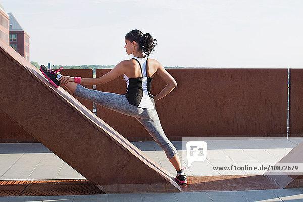 Frau trainiert mit angehobenem Bein an städtischer Fußgängerbrücke lehnend