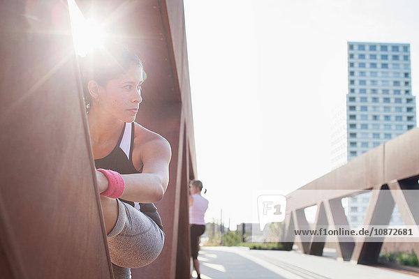 Woman training with leg raised on sunlit urban footbridge