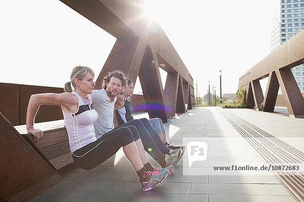 Two women and man push up training against urban footbridge