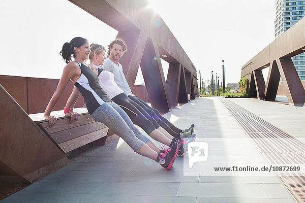 Two women and man push up training leaning against urban footbridge