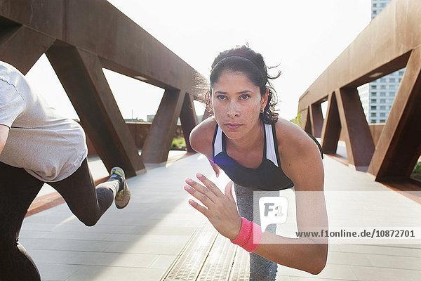 Frau trainiert auf einem Bein auf einer städtischen Fußgängerbrücke