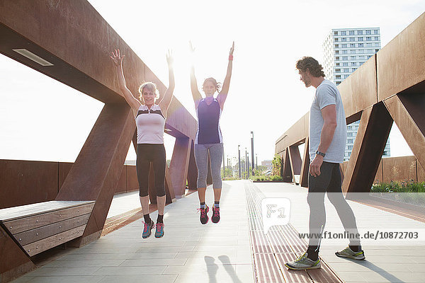 Two women jump training on urban footbridge with male personal trainer