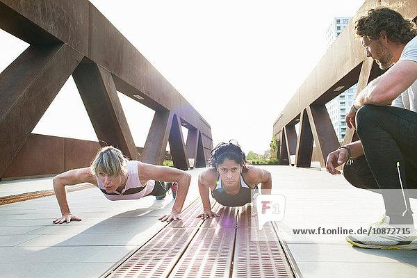 Zwei Frauen machen Push-Ups auf einer städtischen Fußgängerbrücke mit einem männlichen Personal Trainer