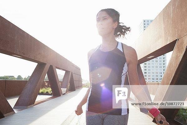 Woman training with skipping ropes on sunlit urban footbridge