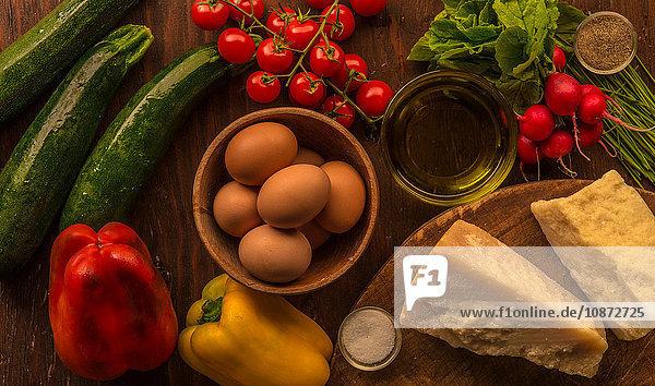 Draufsicht auf rohe und zubereitete Lebensmittel  Parmesan  Eier und Gemüse
