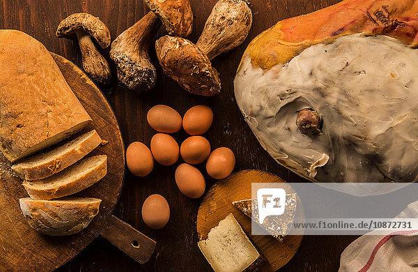 Draufsicht auf rohes und zubereitetes Essen  Käse  Brot  Eier und Steinpilze