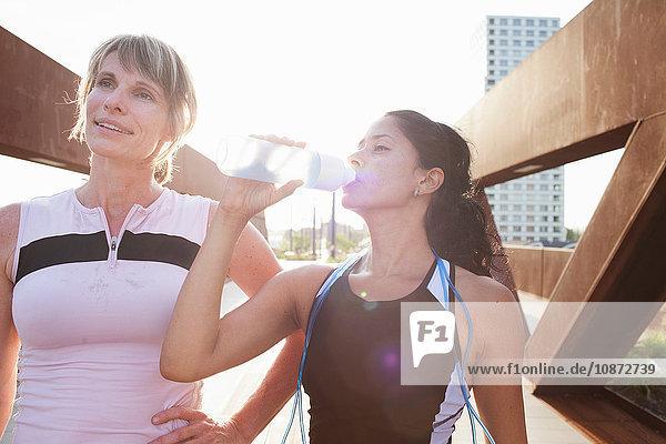 Two women taking a water break from training on urban footbridge