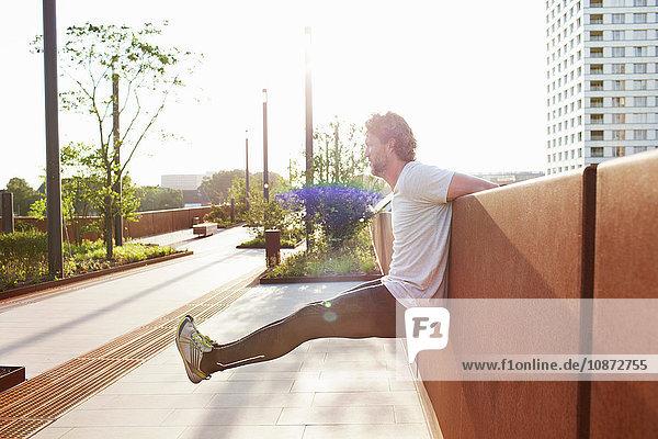 Mann trainiert das Hochheben der Beine auf städtischer Fußgängerbrücke