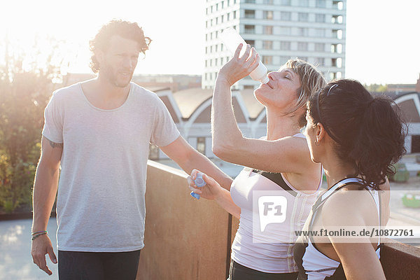 Two women and man training  drinking water on urban footbridge