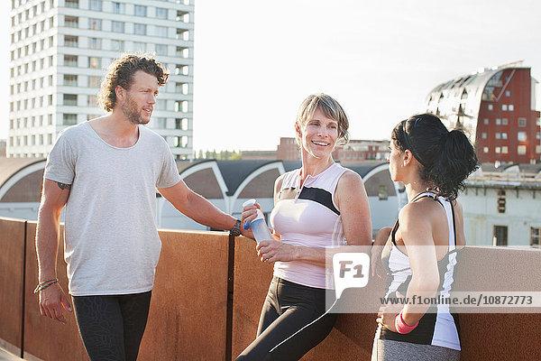 Two women and man training  chatting on footbridge