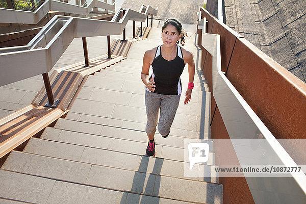 Weibliche Läuferin läuft Stadttreppe hinauf
