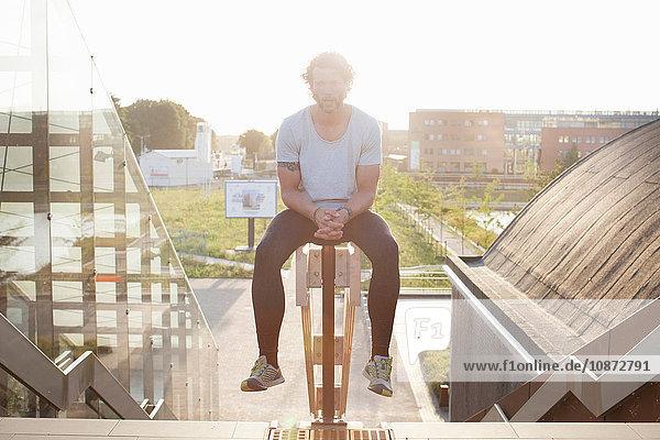 Porträt eines Mannes  der nach dem Training auf dem Geländer sitzt