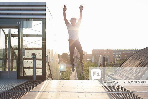 Mann trainiert  springt auf einem Steg in die Luft