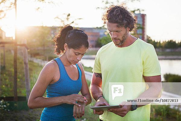 Männlicher Personal Trainer und Frau überprüfen Uhr und digitales Tablet am Flussufer