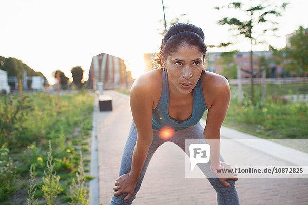 Läuferin macht eine Pause auf dem Bürgersteig