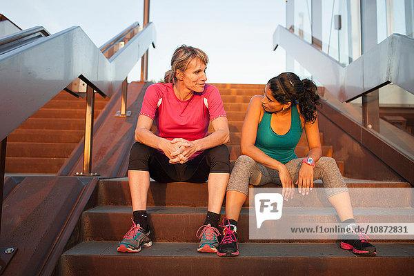 Two women taking a break from training on stairway