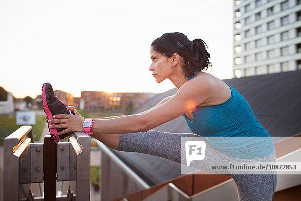 Weibliche Läuferin streckt das Bein auf der Treppe