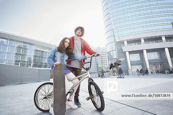 Mädchen und Mann mit BMX und Skateboard im Stadtgebiet
