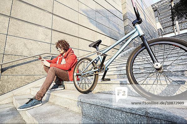 Mann sitzt auf Stufen mit BMX mit Smartphone