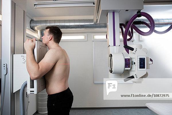 Männlicher Patient  der sich auf eine Röntgenaufnahme vorbereitet