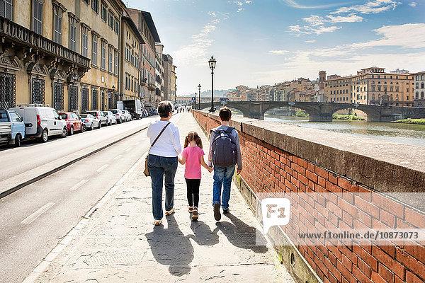 Rückansicht einer älteren Frau und zweier Enkelkinder beim Spaziergang am Arno  Florenz  Italien