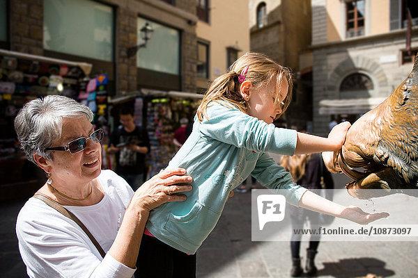 Ältere Frau und Enkelin mit der Hand unter einem Wasserbrunnen  Florenz  Italien