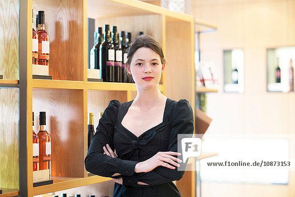 Geschäftsinhaber in Weinladen Arme gekreuzt und in die Kamera blickend