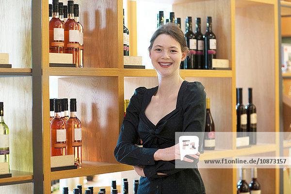 Geschäftsinhaber im Weinladen verschränkt die Arme und schaut lächelnd in die Kamera