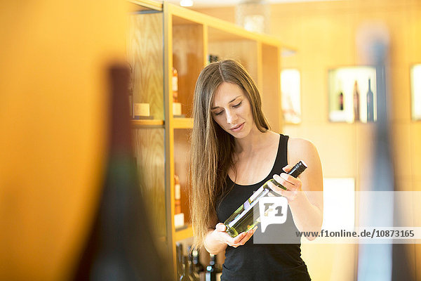 Young woman in wine shop holding bottle of wine