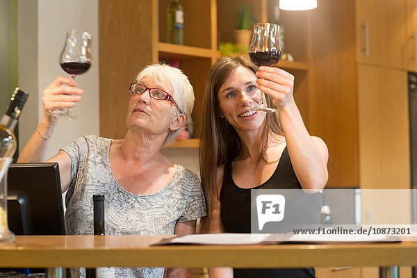Women at counter in wine bar checking clarity of wine
