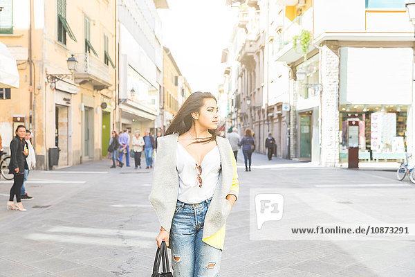 Frau steht auf der Straße und schaut zur Seite