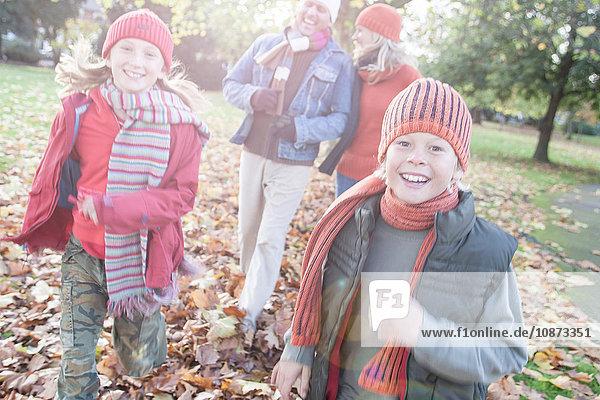 Familie amüsiert sich im Park  spaziert durch das Herbstlaub