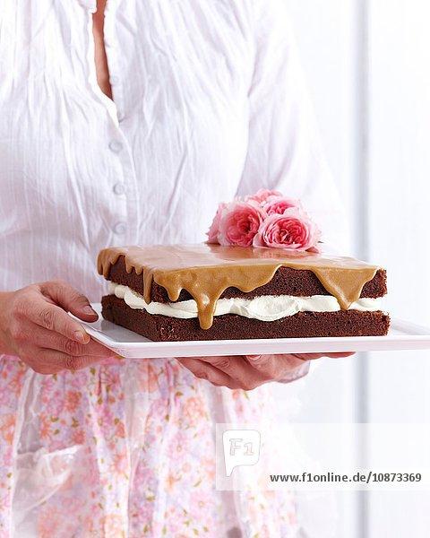 Frau hält blumengeschmückten Schokoladenbiskuit-Kaffee-Kuchen Frau hält blumengeschmückten Schokoladenbiskuit-Kaffee-Kuchen