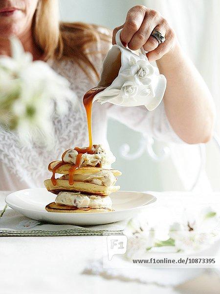 Frau gießt Toffeesauce aus verziertem Krug auf einen Stapel Hechte Frau gießt Toffeesauce aus verziertem Krug auf einen Stapel Hechte