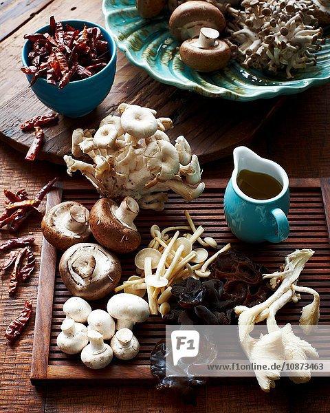 Hochwinkelansicht verschiedener Pilze auf Holzbrett und getrocknete Chillis in Schale