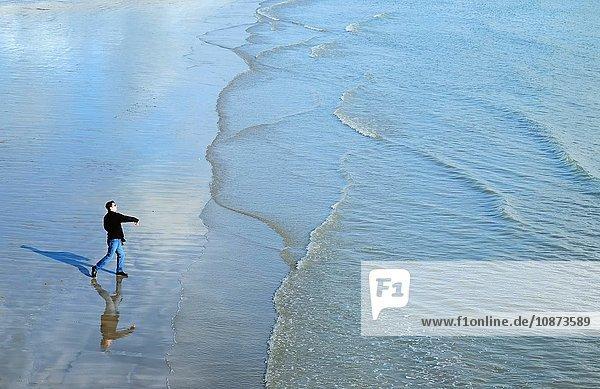 Hochwinkel-Seitenansicht eines reifen Mannes am Strand  der Steine ins Meer wirft
