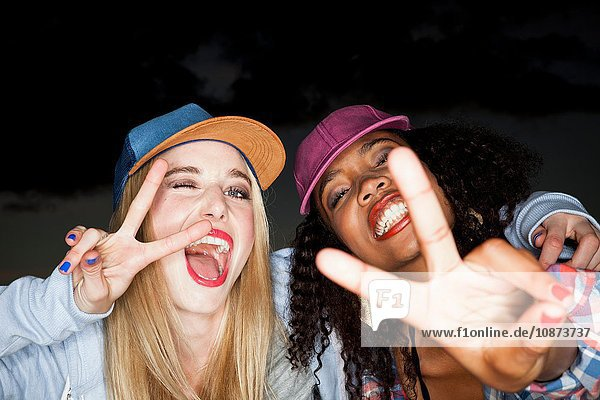 Young woman wearing baseball cap arm around friend looking at camera doing peace sign