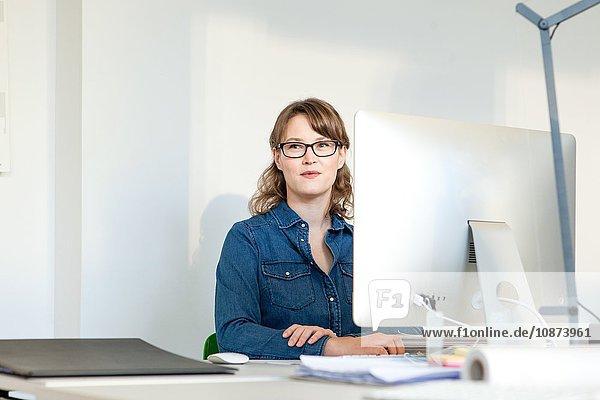 Young woman wearing eyeglasses sitting at desk using computer looking away smiling