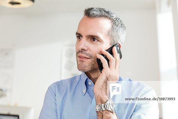 Mature man using smartphone to make telephone call looking away