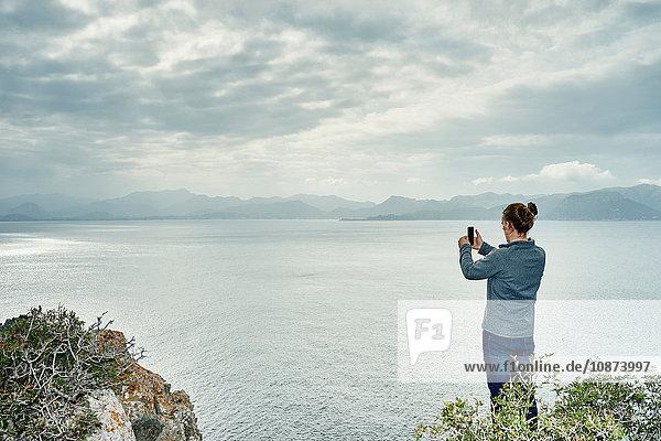 Junger Mann steht auf Klippe und fotografiert mit Smartphone  Alcudia  Mallorca  Spanien Junger Mann steht auf Klippe und fotografiert mit Smartphone, Alcudia, Mallorca, Spanien