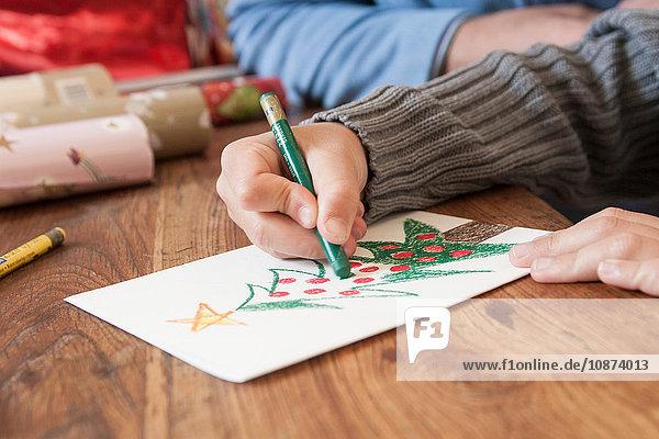 Jungen zeichnen Weihnachtsbaum von Hand