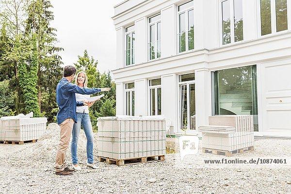 Ansicht des Architekten in voller Länge mit Plänen von Hausbesitzern für die Außenseite des Hauses  zeigt auf