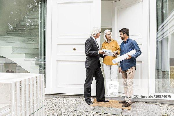 Architekt hält aufgerollte Blaupausen in der Hand und spricht mit Hausbesitzern an der Haustür
